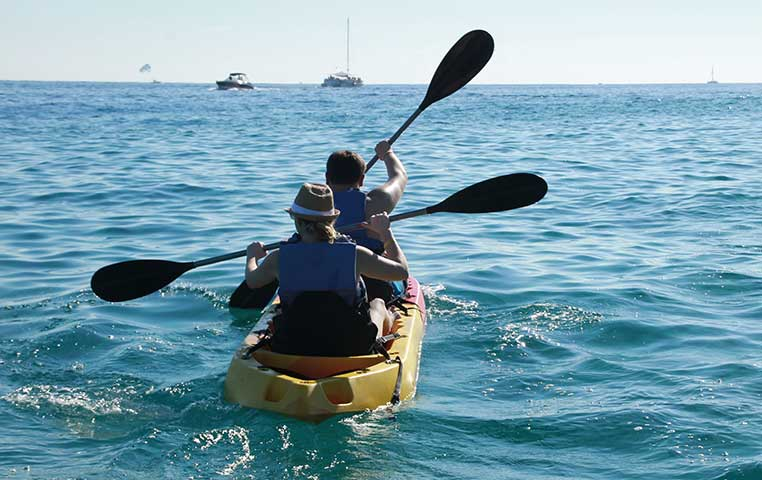 Kayaking out the Ocean in Cabo San Lucas with view to Sail Boats and Fishing Boats