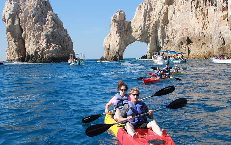 Group of kayaks close to Cabo Arch with Sea Lions in the background