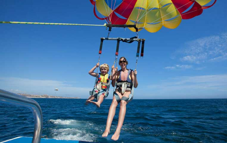 Father and Son in Cabo laughing on a Parasail going up the Sky behind a Boat
