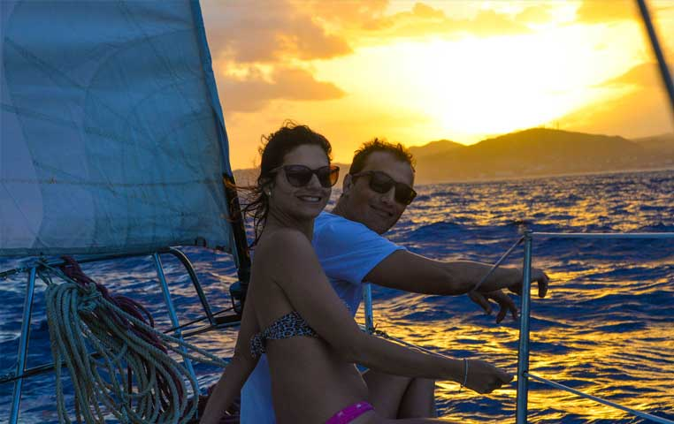 Couple on a Sail Boat with Incredible Sunset behond them by the Cabo Arch
