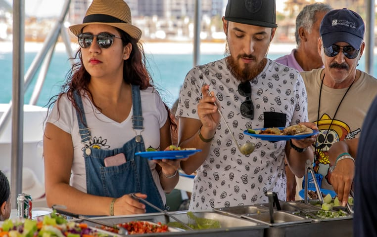 People eating from delicious Buffet on catamaran