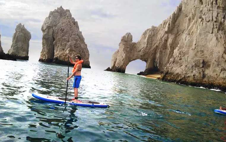 Man standing on a Surf Board with Paddle in front of the Cabo Arch