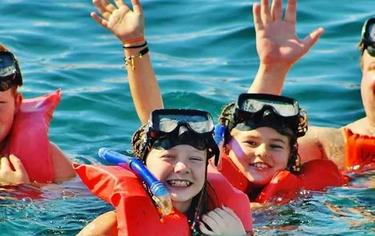 Children with Snorkel gear in the Water of Cabo San Lucas Smiling