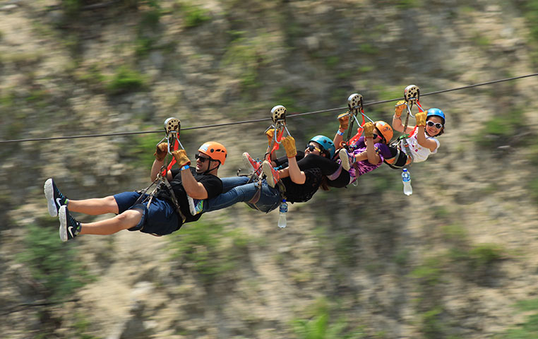 4 people together Zip Lining above a Wild Canyon Oasis in Cabo San Lucas