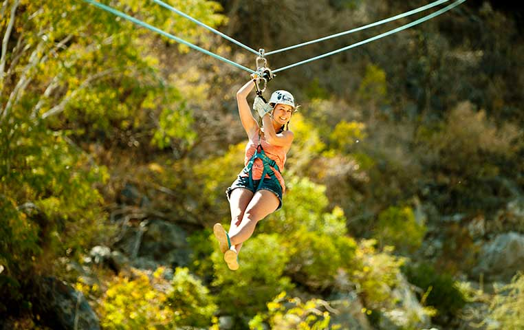 A woman soaring down a Zip Line in a Wild Canyon surounded by Nature