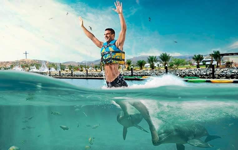 Man hugging a Bottlenose Dolphin in Cabo San Lucas Mexico