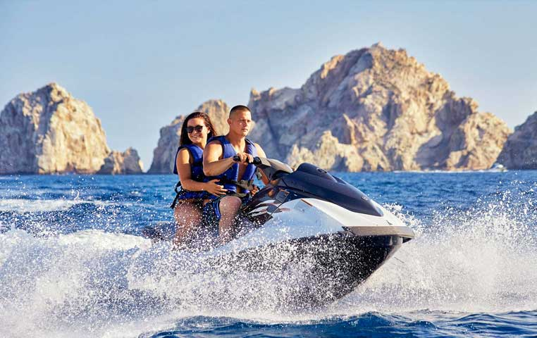 Couple on a Wave Runner happy in front of the Los Cabo Arch