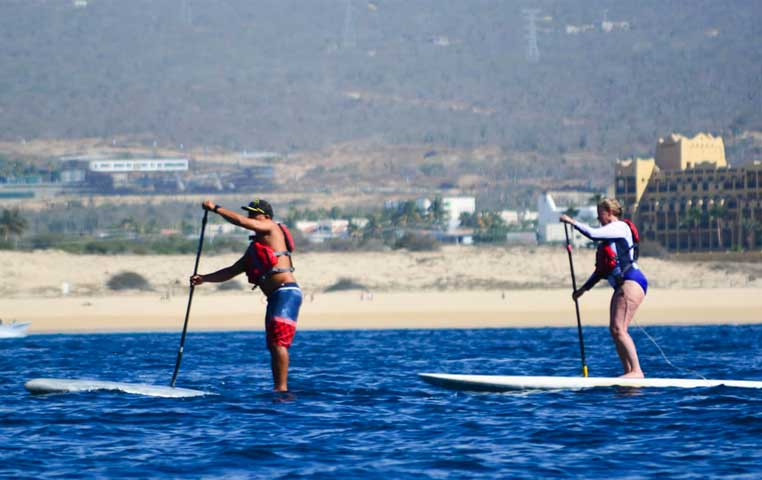 Couple on a Surf up Paddle in front of Riu Santa fe in Los Cabos