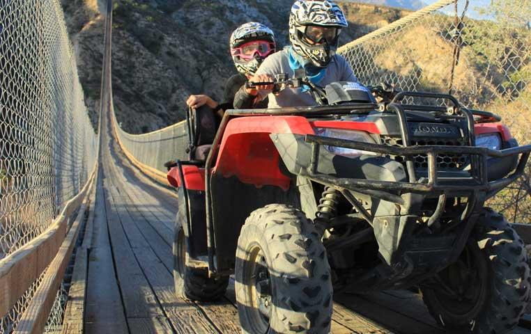 Double ATV racing down a huge Wooden Suspension bridge in Cabo San Lucas